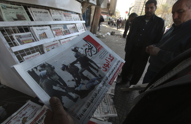 Egyptian man looks at Al Tahrir newspaper featuring front page picture of security forces beating female demonstrator during Saturday's clashes near Tahrir Square in Cairo